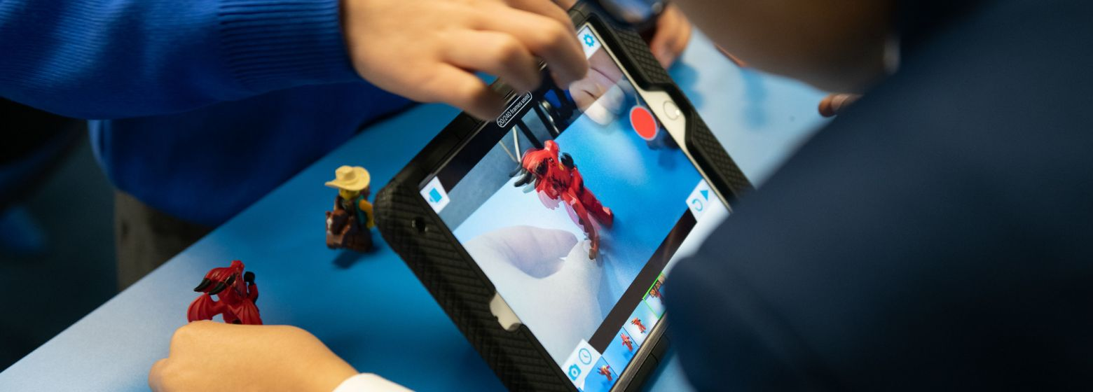 young boy taking photos of toys using a tablet