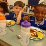3 children eating their school dinners