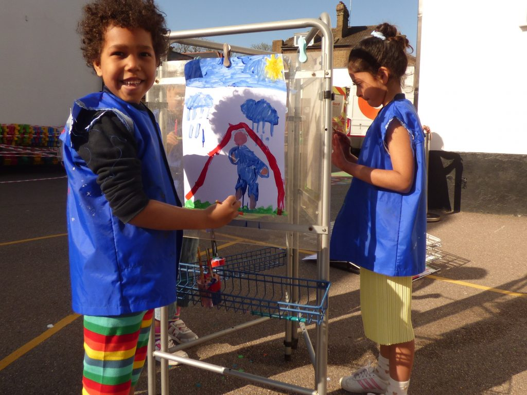 Children painting outside; they're wearing blue vests in case any paint goes onto their clothes