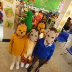 Children wearing elephant and/or lion face masks