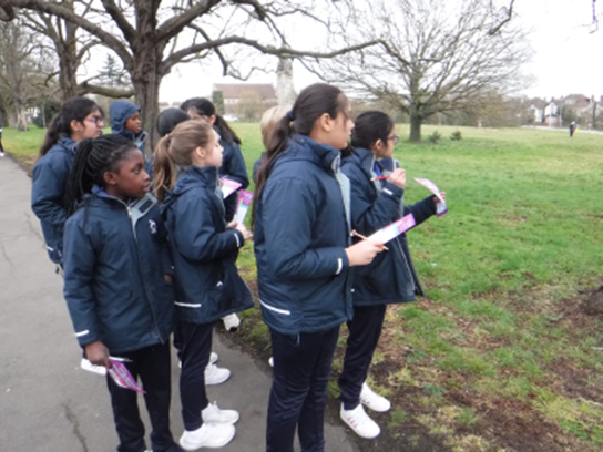 A group of children in uniform coats walking in the park